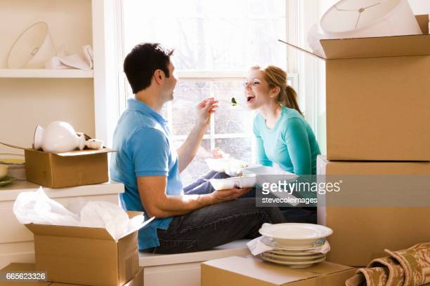 Young couple with surrounded by moving boxes.