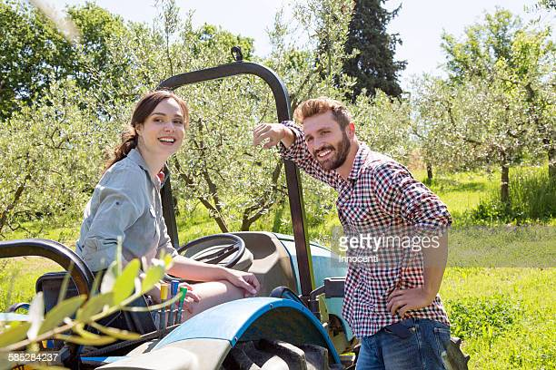 Young couple with tractor looking at camera smiling