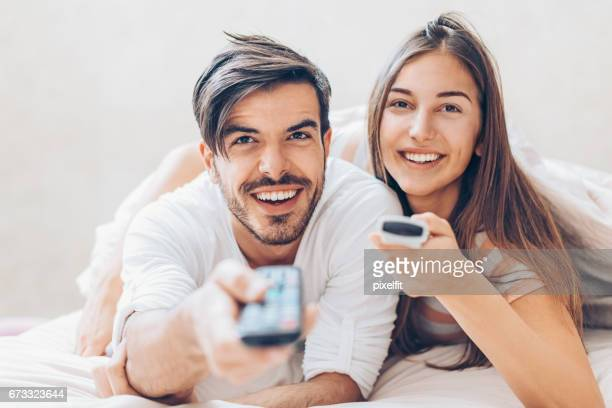 Young couple with two tv remote controls