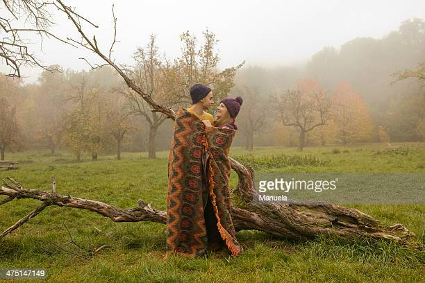 Young couple wrapped in blanket in misty park