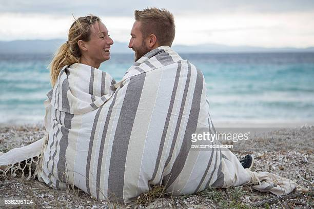 Young couple wrapped in blanket on the beach