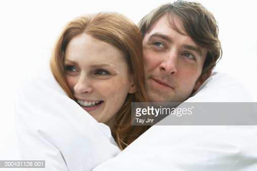Young couple wrapped in duvet, woman smiling, close-up : Foto de stock