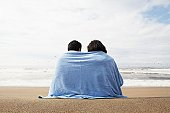 Young couple wrapped in towel on beach (rear view)