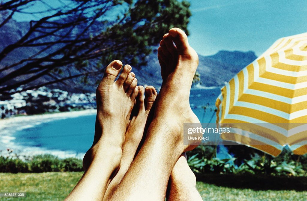 Young couple's bare feet, bay in background (cross-processed) : Stock Photo
