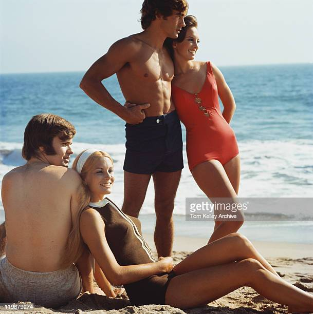 Young couples resting on beach, smiling