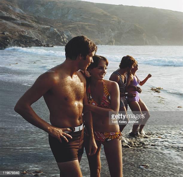 Junge Paare stehen am Strand, die lächelnd