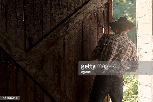 Young Cowboy Closing or Opening Barn Door