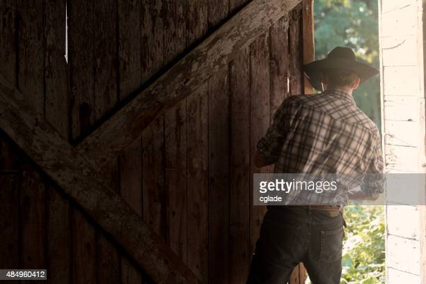 Young Cowboy Closing or Opening Barn Door