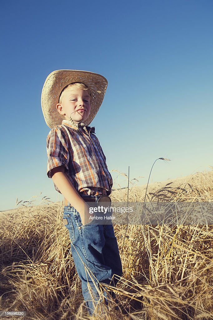 Young cowboy in a wheat field : Stock Photo