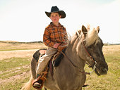 Young cowboy riding pony on prairie in Big Timber, Montana