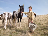 Young cowboy with horses on ranch in Big Timber, Montana in springtime