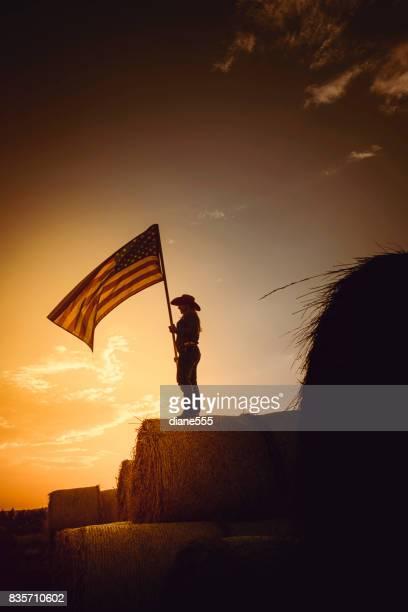 Vaquera joven está parado en la parte superior de una enorme pila de balas de heno al atardecer con la bandera americana