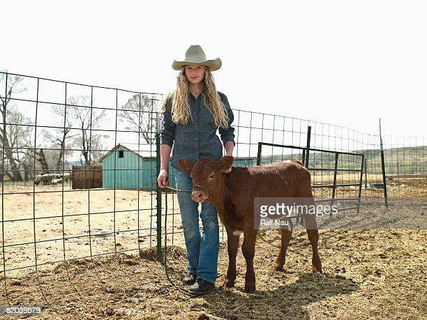 Young cowgirl with calf on ranch