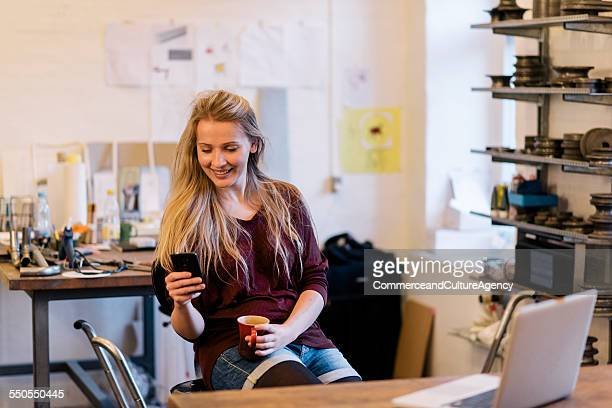 young craftswoman in workshop texting