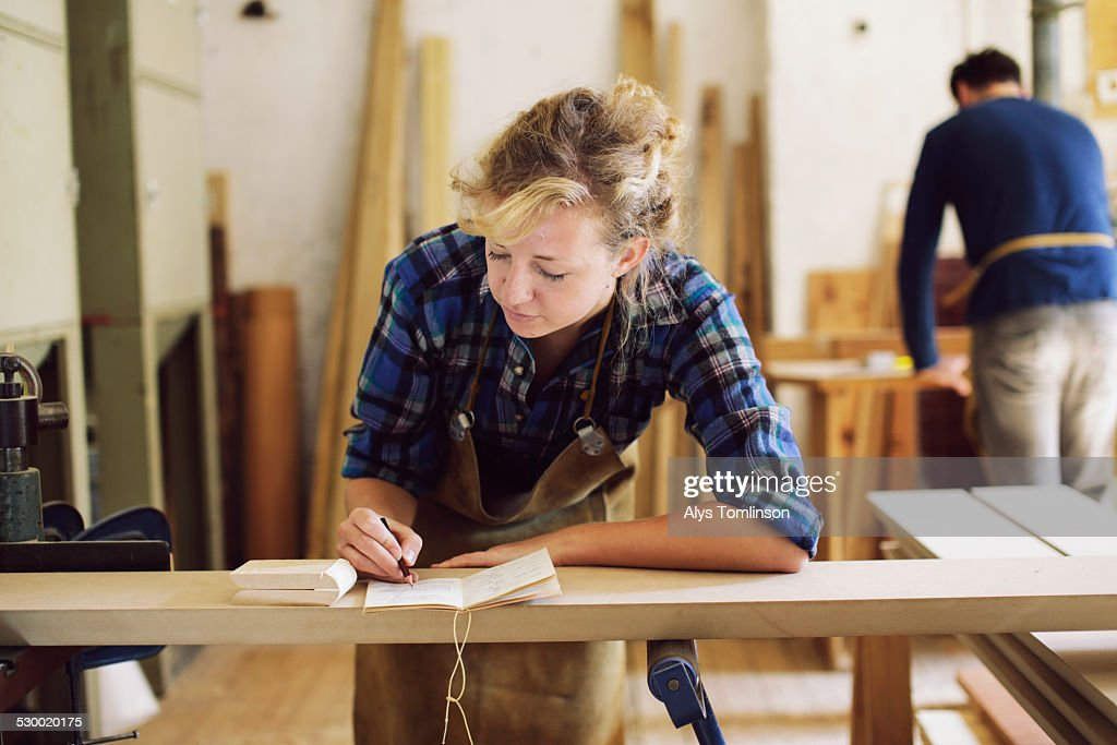 Young craftswoman making notes in pipe organ workshop : Stock Photo