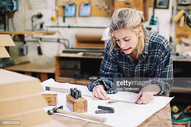 Young craftswoman measuring blueprint on workbench in pipe organ workshop