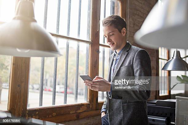 Young creative businessman at the window looking on mobile phone