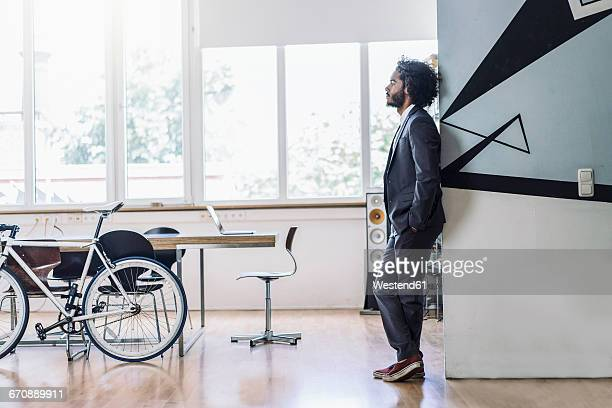 Young creative businessman standing in office, thinking with hands in pockets