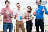 Young creative entrepreneurs being motivated, one woman and three men