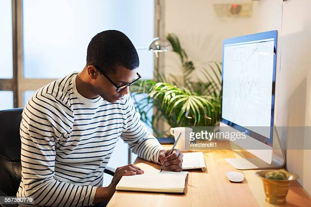 Young creative man sitting at desk writing in his notebook