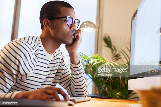 Young creative man working at computer in his home office