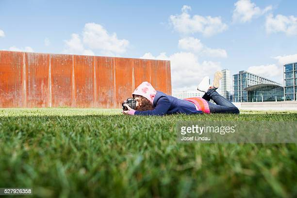 Young creative person laying on gras and taking picture with camera