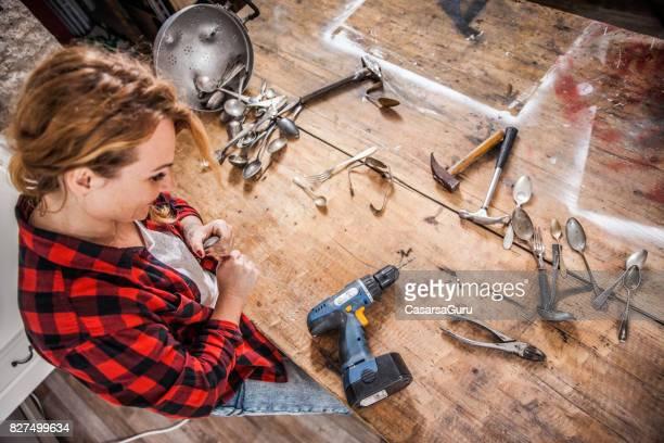 Junge kreative Frau Kunstschaffen mit Schrauben Löffel