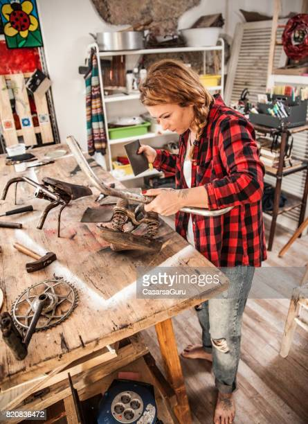 Young Creative Woman Restoring an Old-fashioned Bicycle