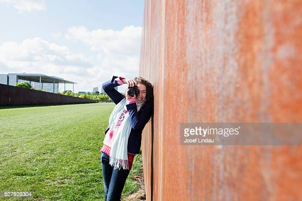 Young creative woman taking pictures with Camera