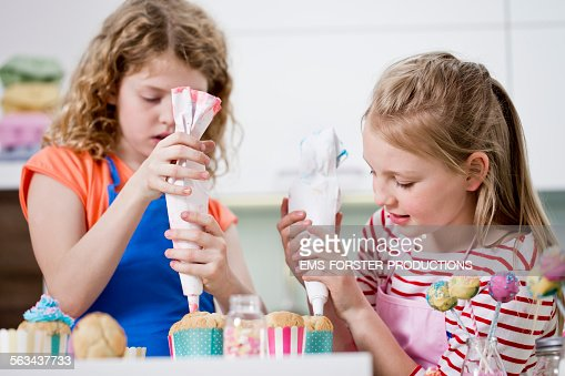 Woman Decorating Cupcakes young girl holding a plate of cupcakes stock photo | getty images