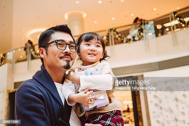 Young dad holding daughter joyfully in mall