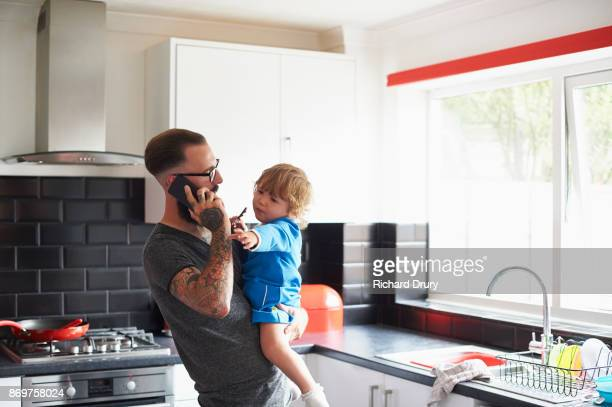 Young dad making phone call and looking after toddler girl