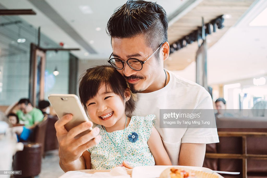 Young dad using smartphone with his little daughter while little daughter sitting on his lap in a coffee shop joyfully
