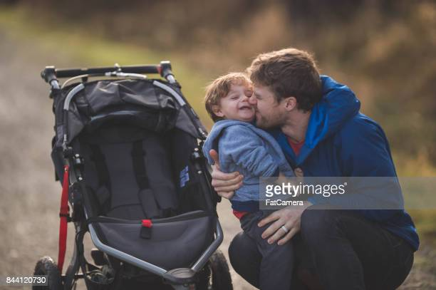 Young dad with boy in stroller