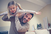 Little girl lying on fathers shoulders. Looking at camera.