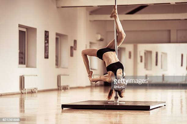 Young dancer doing a closed inside leg hang on pole.