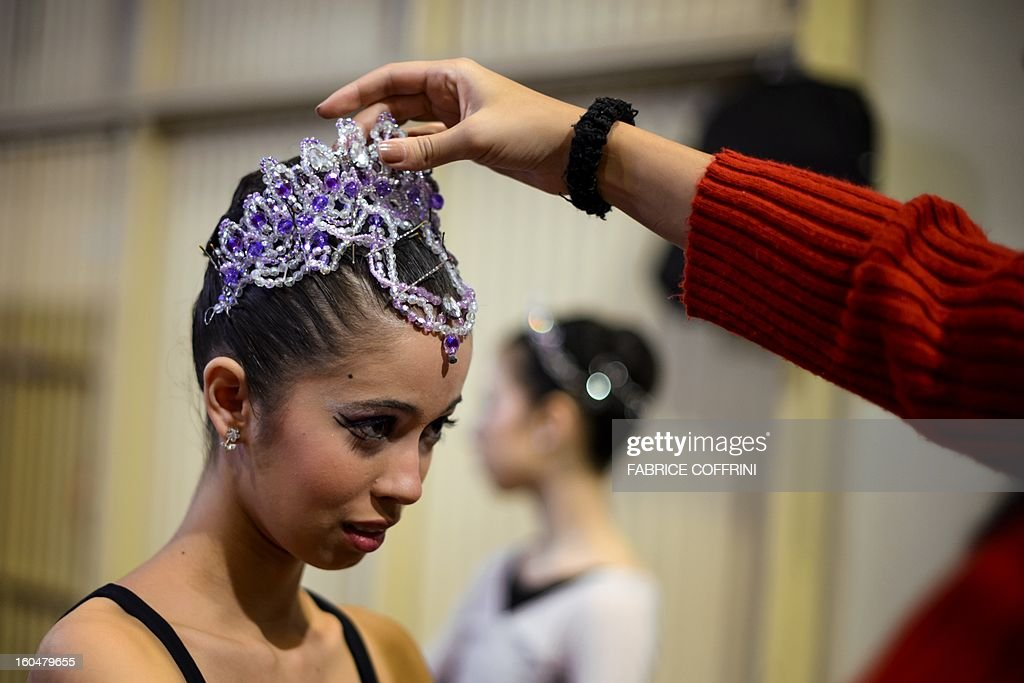A young dancer has her tiara fixed prior to the classical and contemporary selections at the 41st International Ballet Competition 'Prix de Lausanne' on February 1, 2013 in Lausanne. The Prix de Lausanne is an international competition open to young dancers aged 15 to 18 who are not yet professionals. The best finalists win scholarships granting free tuition in a world renowned dance school or dance company. AFP PHOTO/ FABRICE COFFRINI