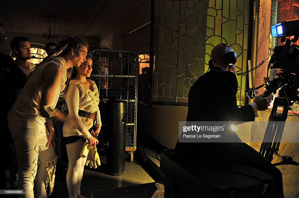 Young dancers look at guests arriving as a television cameraman films the Nobel Banquet after the 2012 Nobel Prize Ceremony at Town Hall on December...