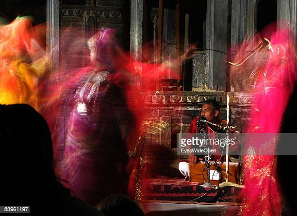 Young dancing Indian women in an Idance show are seen while a traditional musician sings and plays a harmonium on January 06 2008 in Udaipur India