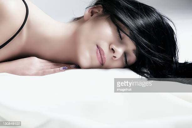 Young dark-haired woman lying with eyes closed, portrait