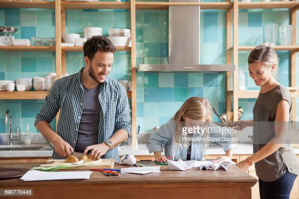 Young daughter drawing at kitchen counter while parents prepare meal