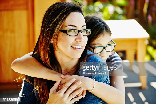 Young daughter embracing smiling mother on patio