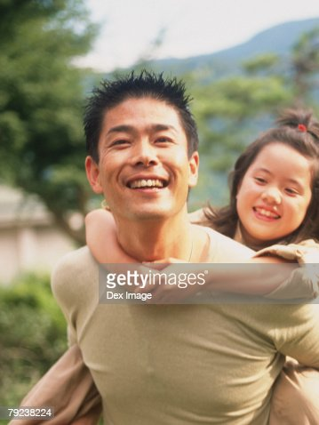 Young daughter having a piggyback from her father : Stock Photo