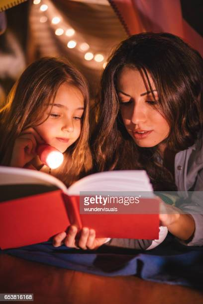 Young daughter listening to a bedtime story by her mother