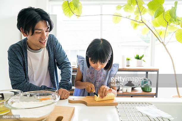 Young daughter looking happy while baking and bonding with father