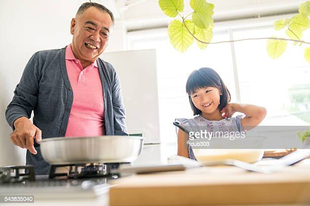 Young daughter making a cake with grandfather