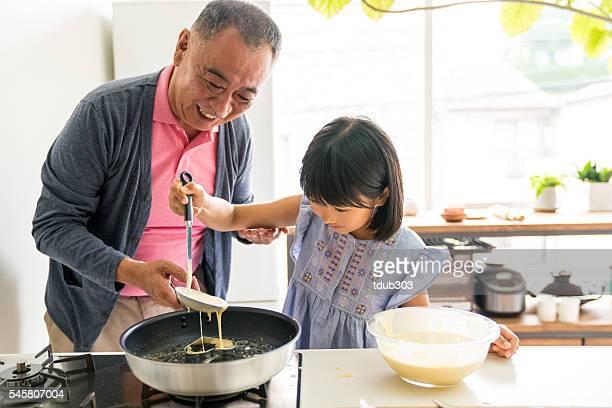 Joven hija haciendo un pastel con abuelo
