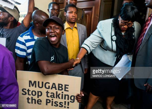 A young demonstrator shakes hand with a member of parliament leaving the National Assembly building on November 21 2017 in Harare as Zimbabwe's...
