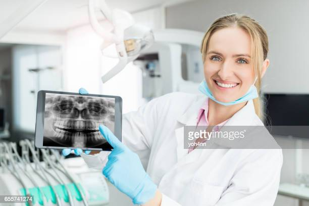 Young dental expert showing x-ray on tablet