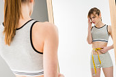young depressed woman measuring her waist and looking at mirror isolated on white